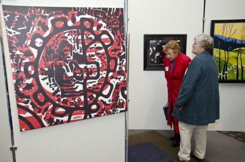"Visitors look over the artwork, including ""Joe Root,"" an ink on canvas by Todd Scalise (left)."