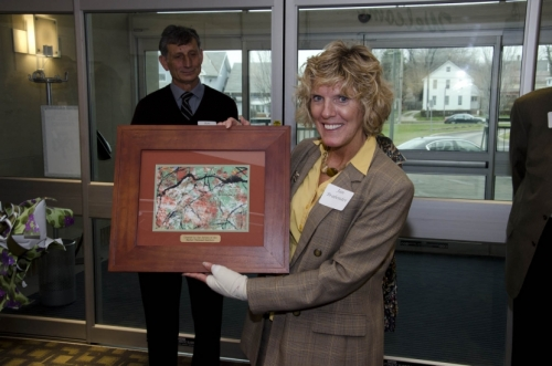 Jan Brabender, who designed and pieced a quilt commemorating the 100th birthday of Dr. Gertrude A. Barber, accepts a gift of appreciation for her work.